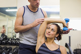 Trainer correcting content woman lifting dumbbells