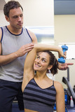 Trainer correcting smiling woman lifting dumbbells
