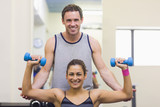 Trainer correcting cheerful woman lifting dumbbells