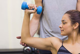 Trainer correcting woman lifting dumbbells