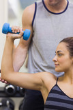 Trainer correcting calm woman lifting dumbbells