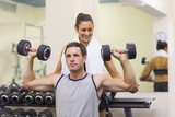 Trainer correcting muscular man lifting dumbbells