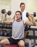 Trainer correcting attractive man lifting dumbbells