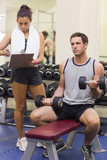 Trainer taking notes of muscular man lifting dumbbells