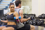 Woman and man lifting dumbbells