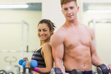 Topless man and smiling woman lifting dumbbells