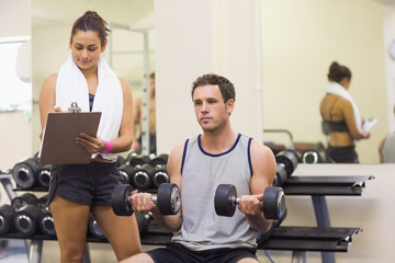 Trainer taking notes of attractive man lifting dumbbells
