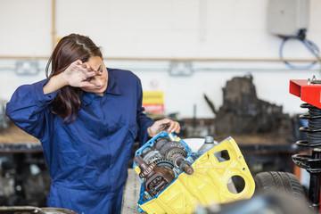 Exhausted trainee repairing engine