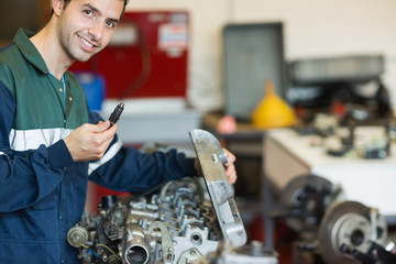 Smiling repairman repairing an engine