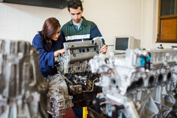 Trainee and instructor repairing an engine