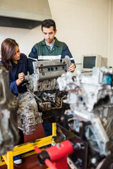 Focused trainee and instructor repairing an engine