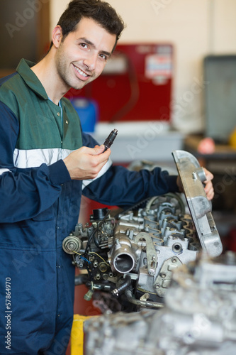 Happy repairman repairing an engine