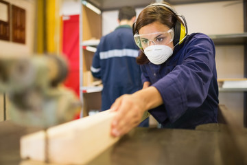 Focused trainee wearing safety protection using a saw