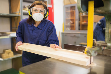 Apprentice wearing safety protection using saw