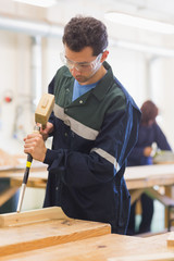 Carpenter using mallet and chisel