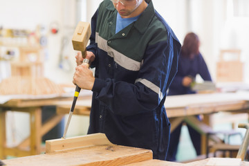 Craftsman using mallet and chisel