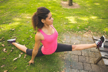 Flexible young woman doing the splits exercise in park