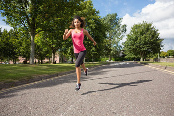 Full length of a healthy woman jogging on pathway in park