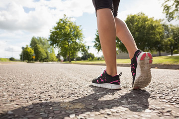 Low section of a sporty woman jogging on pathway in park