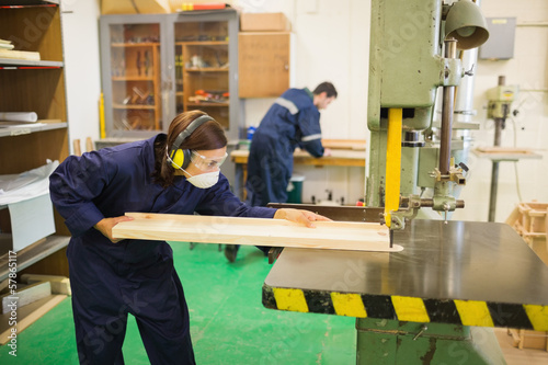 Concentrating trainee wearing safety protection using a saw