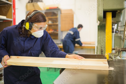 Serious trainee wearing safety protection using a saw