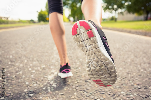 Low section of sporty woman jogging on pathway in park