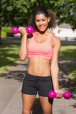 Smiling fit woman exercising with dumbbells in park