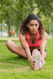 Portrait of a beautiful sporty woman stretching her leg in park