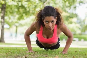Beautiful serious young woman doing push ups in park