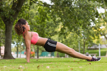 Toned young woman doing stretching exercise in park