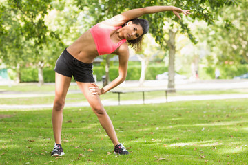 Toned and flexible woman doing stretching exercise in park