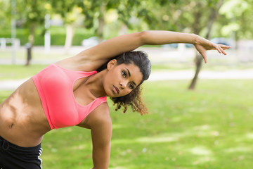 Toned woman doing stretching exercise in park