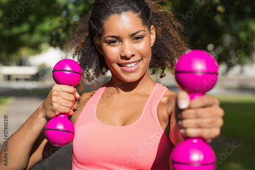 Smiling fit young woman exercising with dumbbells in park