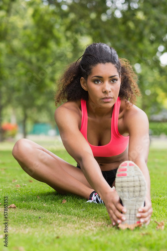 Beautiful sporty woman stretching her leg in park