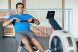 Man working out on row machine in fitness studio