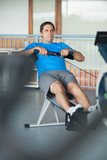 Determined man working out on row machine in fitness studio