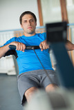 Determined man working out on row machine