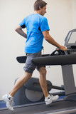 Healthy man running on treadmill at fitness studio