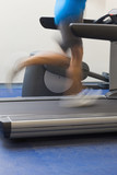 Low section of a healthy man running on treadmill