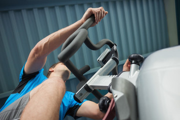 Determined man working out at spinning class in gym