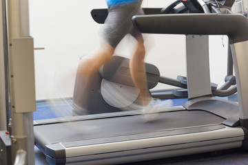 Low section side view of a healthy man running on treadmill