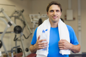 Portrait of a smiling man with water bottle in the gym