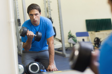 Determined man with dumbbell in fitness studio