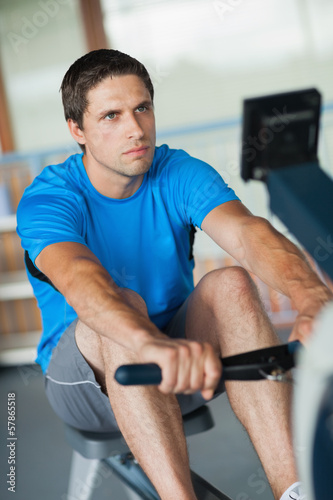 Determined young man working out on row machine