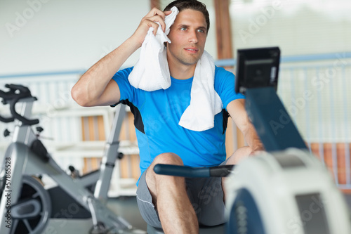 Tired young man working out on row machine