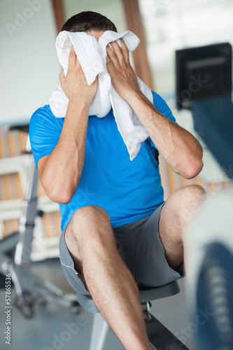 Tired man wiping face while working on row machine