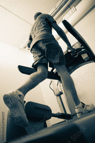 Low angle view of a healthy man running on treadmill