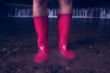 Low section of woman in red gumboots in water
