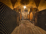 wine cellar with bottles and oak barrels