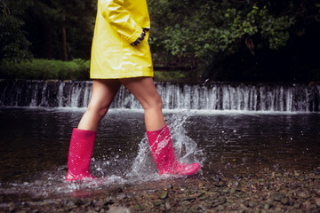 Woman in yellow raincoat and red gumboots against waterfall